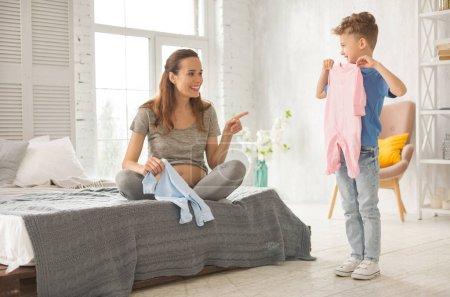 Photo pour En venant de la mère. Bouclés petit garçon portant élégant blanc baskets venant à sa mère enceinte assis sur grand lit double - image libre de droit
