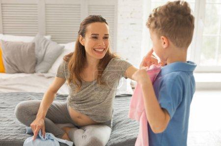 Photo pour De nombreux oreillers. Femme enceinte largement souriante détendu tout en étant assis sur le lit avec beaucoup de coussins colorés - image libre de droit