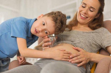 Photo pour Garçon intéressé. Intéressées garçon frisé se sentant extrêmement curieux tout en touchant le ventre enceinte de mère assise dans le fauteuil - image libre de droit