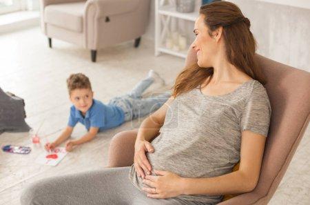 Photo pour Se sentir soulagé. Belle femme enceinte se sentant extrêmement soulagé tout en regardant les fils adorable doux - image libre de droit