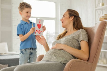 Photo pour Photo de peinture. Prendre soin des fils aimant se sentir extrêmement merveilleux tout en image de la peinture pour sa mère enceinte - image libre de droit