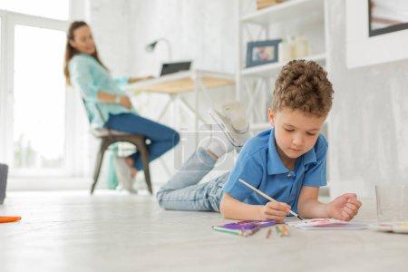 Photo pour Peinture à l'étage. Mignon garçon peu intelligent se sentant divertis en position couchée sur la peinture de plancher avec des couleurs de l'eau - image libre de droit