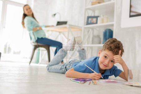 Photo pour Fils bleus. Bouclés fils bleus, se sentant très étonnant alors que de peindre des tableaux avec des couleurs d'eau allongé sur le sol - image libre de droit
