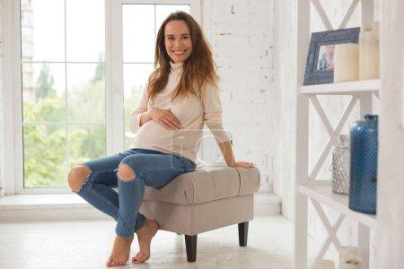 Photo pour Jeans élégants. Rayonnant attente femme portant des jeans élégants sentir incroyablement heureux assis dans le salon - image libre de droit