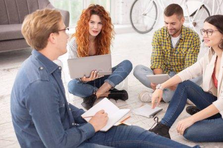 Photo pour Discussion de groupe. Joyeux quatre étudiants communiquant et assis sur le sol - image libre de droit