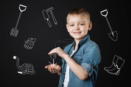 Photo pour Petit jardinier. Joyeux garçon aimable en prenant soin d'une petite fleur dans ses mains lors de la planification pour les cultiver - image libre de droit
