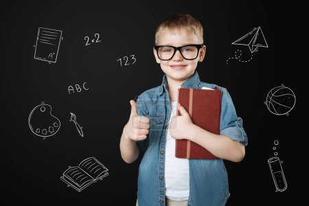 Loving school. Cheerful diligent pupil holding a notebook and putting his thumb up while enjoying going to school