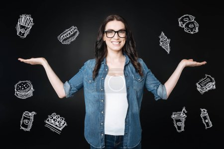 Cheerful woman showing delicious fast food while feeling hungry