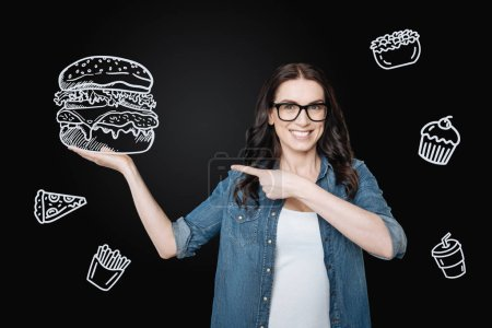 Hungry woman feeling excited while ordering a giant hamburger