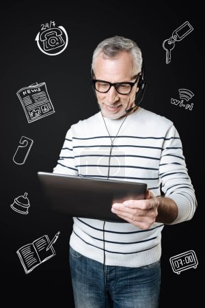 Photo for Receiving video calls. Handsome mature manager holding a modern tablet and looking at the screen of it while wearing convenient headphones and having a video call - Royalty Free Image