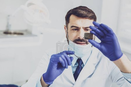 Concentrated stomatologist doing roentgen checkup