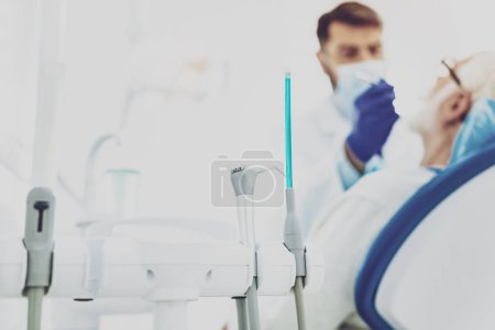 Photo pour Prêt à l'emploi. Silhouette du dentiste compétent qui porte un masque lors de l'examen de son visiteur - image libre de droit