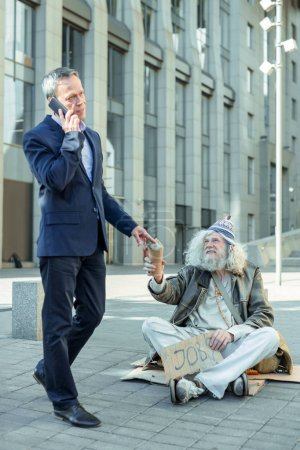 Busy businessman talking by phone helping homeless vagrant