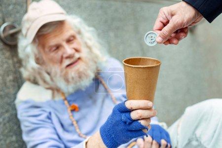 Sympathetic friendly stranger giving token for street man