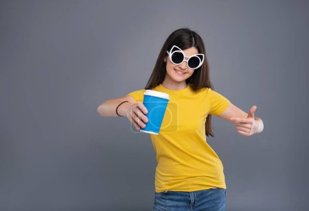 Upbeat teenage girl pointing at coffee cup