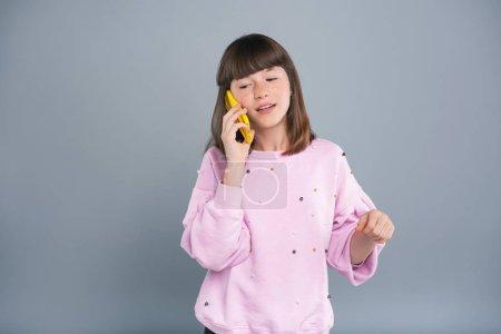 Pleasant teenage girl making a phone call