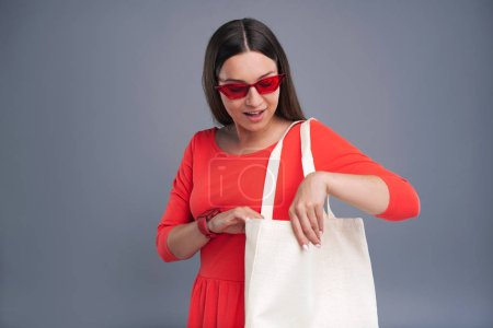 Fashion icon. Attractive dark-haired woman in a red dress wearing red glasses and checking the content of her tote bag