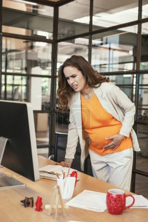 Stressed pregnant CEO suffering from muscle cramp
