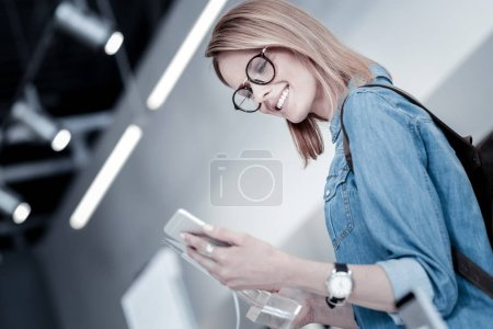 Curious young woman looking at the new gadget
