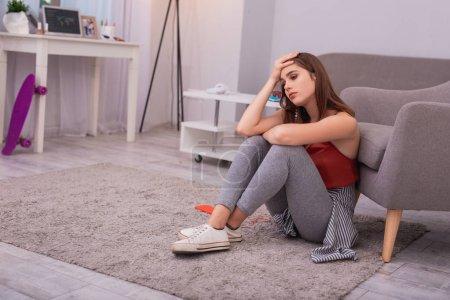 Foto de Echo de menos. Triste chica adolescente tocando la cabeza y sentado en el piso - Imagen libre de derechos