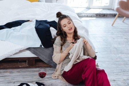 Foto de Ex esposa. Ex esposa sentado en el suelo junto a la cama con unas tijeras cortando mucha ropa después de beber vino tinto - Imagen libre de derechos