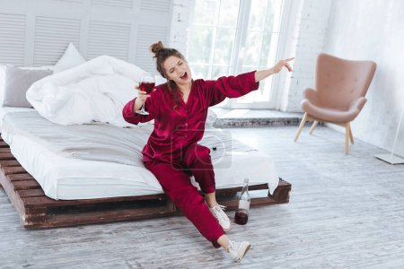 Businesswoman wearing white sneakers and dark-red pajama
