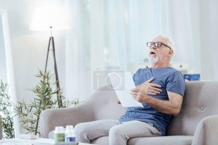Astonished senior man having heartburn