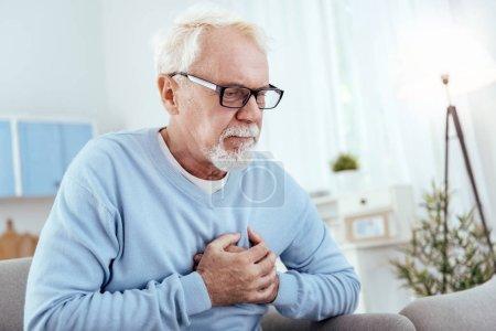 Focused senior man having heart problem