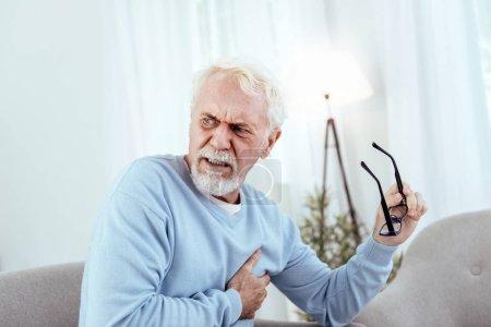 Concerned senior man having chest pain