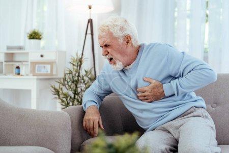 Unhappy senior man having cardiovascular disease
