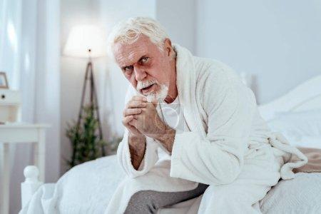 Photo pour Souffrances émotionnelles. Earnest homme senior assis sur le lit et regarder la caméra - image libre de droit