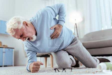 Severe pain. Low angle of shocked senior man shout...