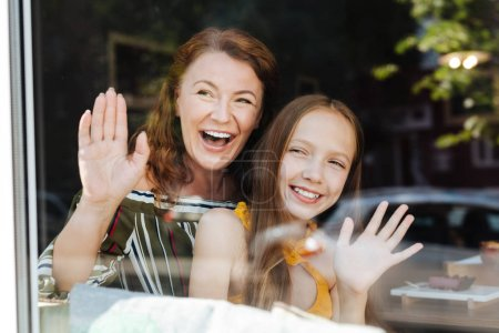 Beaming mother and daughter waving their father