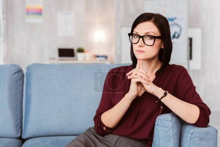 Clever businesswoman. Professional elegant businesswoman wearing glasses and touching her chin while thinking about a new project