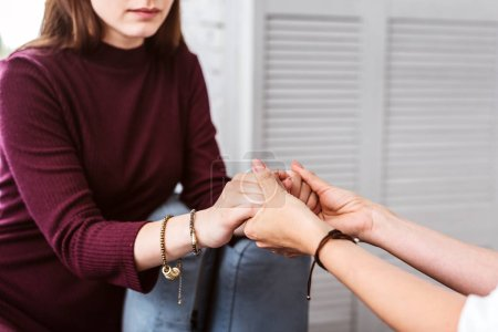 Young woman holding hands with her psychologist and feeling safe