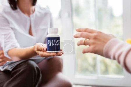 Photo pour Prendre des pilules. Gros plan d'un omnipraticien professionnels donnant une boîte de pilules à un patient souffrant d'insomnie - image libre de droit