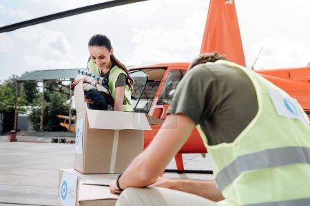 Photo pour Fondation du bénévolat. Ambitieux deux volontaires posant près d'hélicoptère et d'étudier des boîtes - image libre de droit