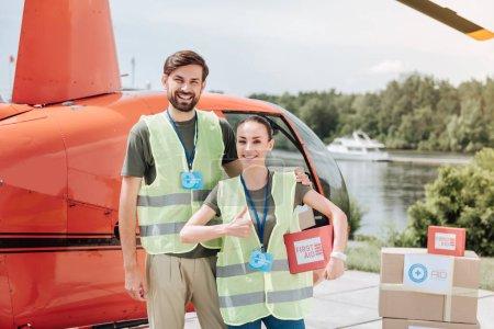 Photo pour Aide pour tout le monde. Jovial deux volontaires restant à proximité des hélicoptères et des caresses - image libre de droit