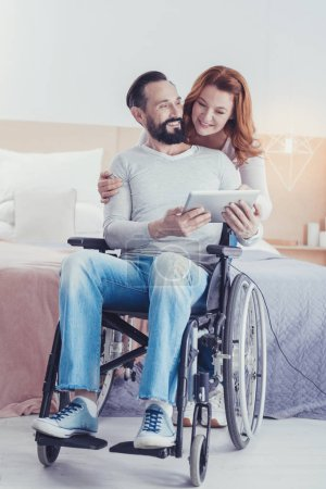 Positive man sitting in a wheelchair and looking happy with new device