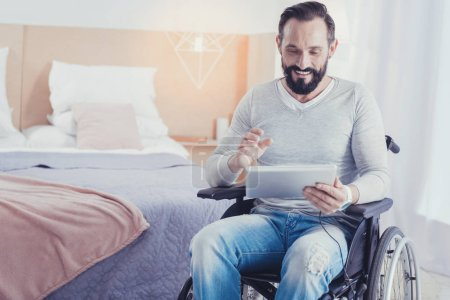 Emotional disabled man holding a tablet while having a video call