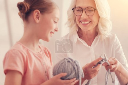 Kind elderly lady enjoying her leisure time with granddaughter