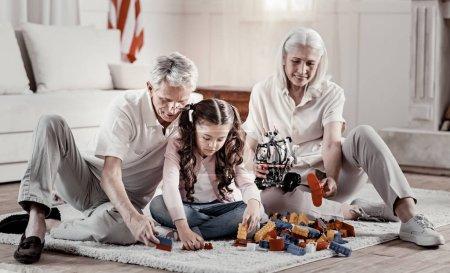 Kind grandparents recreate with focused granddaughter
