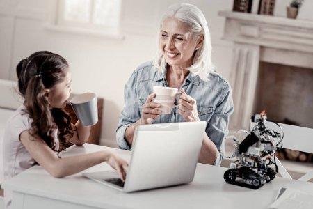 Sharing impressions. Cheery admiring cute granddau...