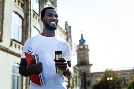 Delighted mulatto standing near his university