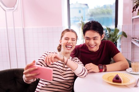 Laughing girlfriend making memorable selfie with her man