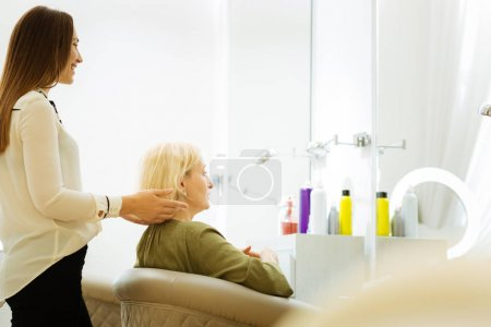 Cheerful positive hairdresser standing behind the client