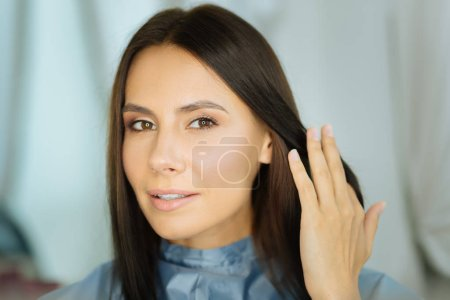 Photo for Beautiful face. Portrait of a beautiful young woman looking at you while touching her hair - Royalty Free Image