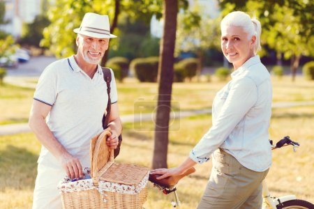Photo for Found a perfect place for our date. Waist up shot of a relaxed retired couple looking into the camera with cheerful smiles on their faces while standing at a bicycle and opening a picnic basket. - Royalty Free Image