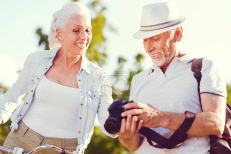 Radiant senior couple smiling while looking though photos