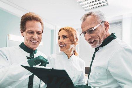 Three experienced bioengineers having informational meeting